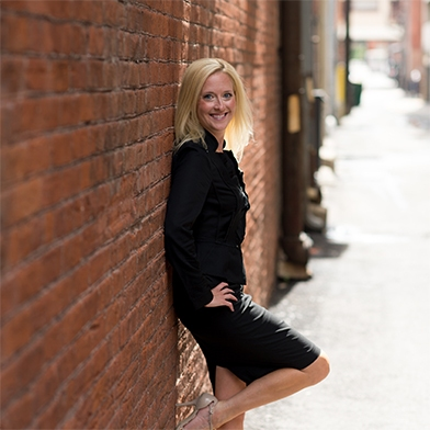 Monica Kerber leaning against a brick wall in a black skirt suit.