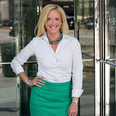 Monica Kerber smiling, wearing a white blouse and a green pencil skirt.